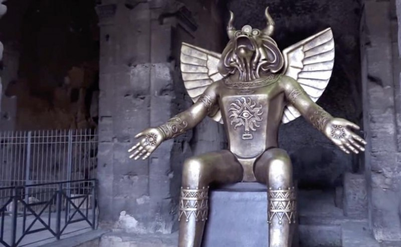 O deus pagão Moloch colocado ao lado de uma placa de exposição no Coliseu, Roma, 27 de setembro de 2019.