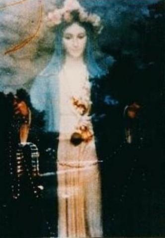 Em San Damiano (Itália), uma mulher fotografou a figura em frente ao portão, uma estátua de Maria. Esta maravilhosa Madonna surgiu quando a foto foi revelada. As linhas vermelhas no canto superior esquerdo simbolizam o cálice com a Santa Hóstia.