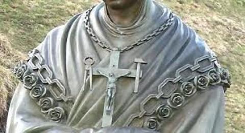 Os braços do crucifixo carregam os instrumentos da Paixão: o martelo, símbolo do pecado, que serviu para pregar Jesus à cruz, e a torquês, símbolo da conversão e da libertação, que serviu para tirar Jesus da cruz.